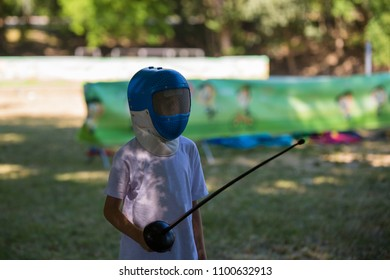 Child with White Shirt Playing Outdoor with Sword and Fencing Mask