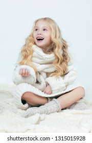 A child in a white warm sweater, sitting and holding a bird feather in his hand, laughs.