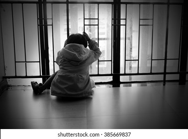 Child who has trapped is look like a very sad sit and looking light far from window.