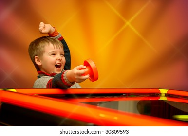 A child who has won his air hockey game, with a red mallet in his hand.