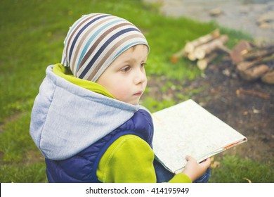 The child who is traveling is looking at a map sitting near a fire in a clearing.