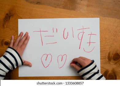 Child who write I love you in Japanese on paper