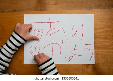 Child who write thank you in Japanese on paper