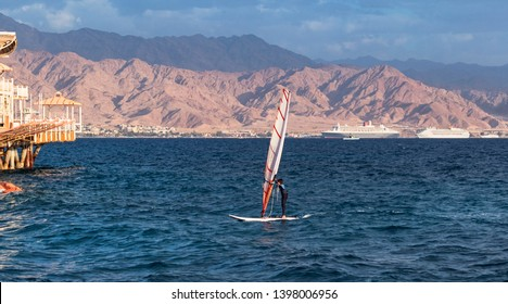 a child windsurfer sailing into the eilat marina in israel with the port of akaba jordan in the background
