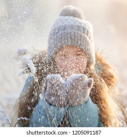 Child at winter. Happy girl outdoors blows on snow