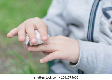 The child wipes his hands with disposable wet wipes