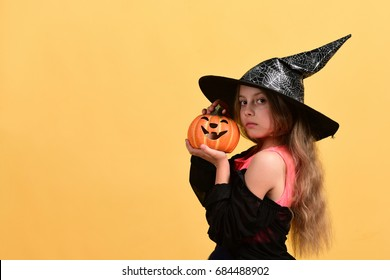 Child in witch costume and jack o lantern. Kid in black witch hat, dress and solemn face. Girl with carved orange pumpkin isolated on warm yellow background. Halloween and celebration concept