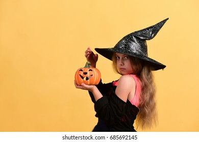 Child in witch costume and jack o lantern. Girl with carved orange pumpkin isolated on warm yellow background. Halloween and costume party concept. Kid in black witch hat, dress and serious face