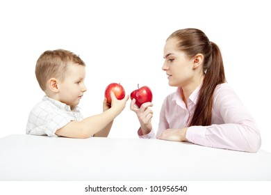 A child, woman and apples. The boy and woman sit facing each other and compare the fresh, red apples.