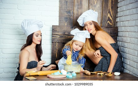 Child and women kneading dough. Brother and sisters at table using kitchen utensils. Happy family and childhood concept. Homemade baking and cooking. Boy and girls in chef hats.
