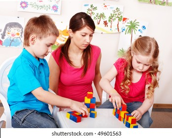 Child with wood block  in play room. Preschool.