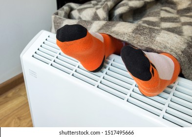 A child with a woolen blanket warms his feet over an electric heater. Symbolic image of cold and flu, home heating in the cold season. Close-up, selective focus.