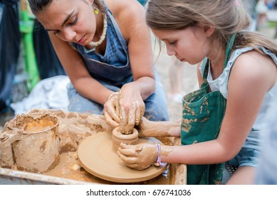 Child working with clay using pottery wheel