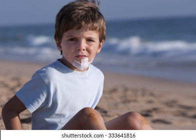 Child, with a wound on the chin, on the beach