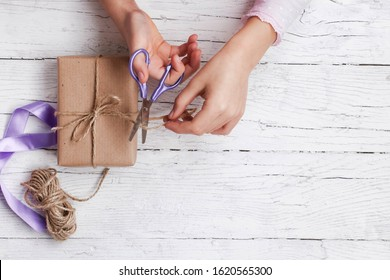 Child is wrapping gift box in brown kraft paper. Present on white wooden background. Kid cuts ribbon with lilac scissors. Close up of hands. Flat layout. Happy spring holidays. Copy space.