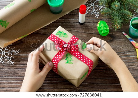a child wraps paper with christmas gifts box and a snowman of sweets made by