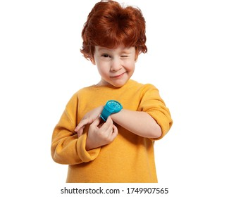 A child with a wristwatch. The red-haired boy shows the time on his watch and squints funny. Portrait of a happy child on a white background. Learning to determine time. Time management.