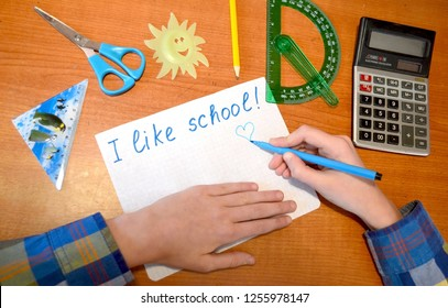 """The child writes: """"I like school"""" on a checkered sheet of paper."""