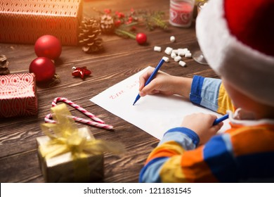 Child writes the letter to Santa Claus on wooden background with decorations.