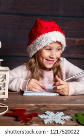 Child writes letter to Santa Claus . Funny girl in Santa hat writes letter to Santa at home