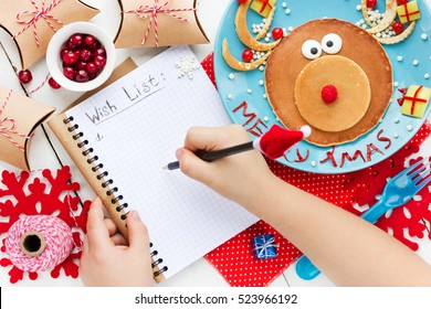Child writes letter for santa, wish list to Christmas on table with gifts and reindeer pancake