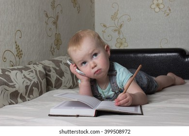 child writing in a notebook talking on the phone
