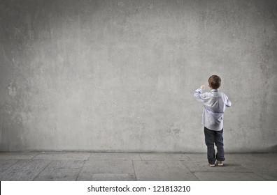 Child writing on a dark white wall