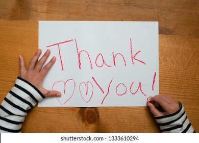 A child writing thank you on paper