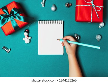 Child writting a letter to Santa. Christmas gift boxes wrapped in red paper on blue frozen background. Bright and festive Christmas concept. Top view, flat lay. Copy spce for text.