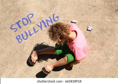 A child wrote Stop Bullying on the sidewalk with chalk. The little boy is sad, writing about being bullied at school. Bullying concept, school bullying, awareness, prevention education
