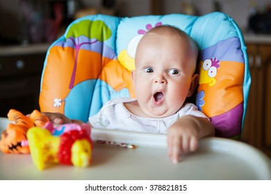 child yawning in a high chair