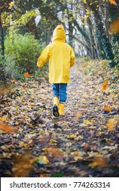 Child with Yellow Rain Boots Playing outdoors in an Autumn Forest enjoying nature with Falling Leaves