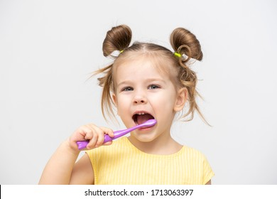 child in a yellow T-shirt with clean teeth brushing on a light background