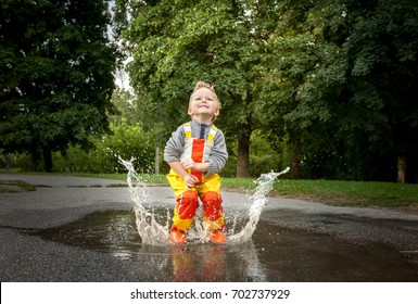 Child in a yellow waterproof coat in the rain jumping in puddles. A boy stands with his head bowed in rain, a bright raincoat. Kid playing autumn park. Outdoor fun by any weather