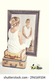 Child or young girl staring at herself in a mirror, sitting on vintage luggage, with a fish tail braid in her hair. Vintage or retro filter applied.