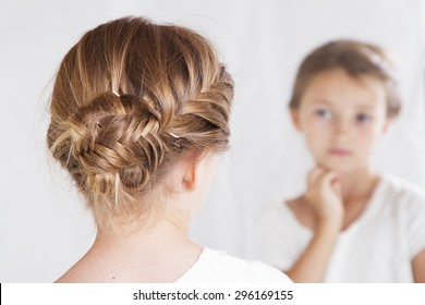 Child or young girl staring at herself in a mirror, with a fish tail braid in her hair.