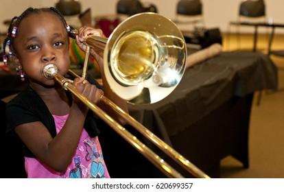 A child/black girl playing a trombone