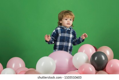 Childen's goods. Happy child on a green background. The little boy is playing with pink balls. Children's background