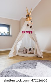 Childen's room corner with a beautifully decorated play tipi tent and a round grey carpet