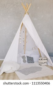 Childen's room with a decorated play tipi tent. Scandinavian style. Wigwam. Boho styled cozy hut with decor.