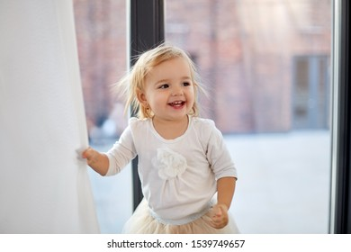 childhood, babyhood and people concept - happy smiling baby girl at home window