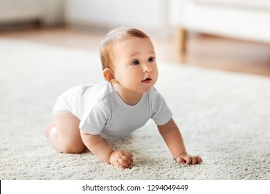 childhood, babyhood and people concept - little baby crawling on floor at home