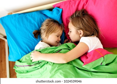 childhood, bedtime and family concept - happy little girls or sisters sleeping in bed at home