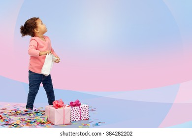 childhood, birthday, party, holidays and people concept - happy little african american baby girl with gift boxes and confetti playing with shopping bag looking up over pink and violet background