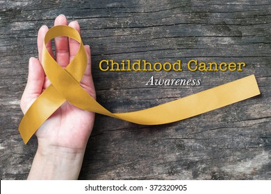 Childhood cancer awareness gold ribbon on human helping hand on old aged wood background