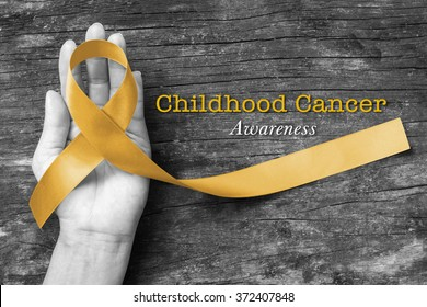 Childhood cancer awareness gold ribbon on helping hand on old aged wood background