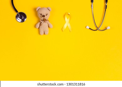 Childhood Cancer Awareness Yellow Ribbon with toy bear and stethoscope on yellow background with copy space. Childhood Cancer Day February, 15.