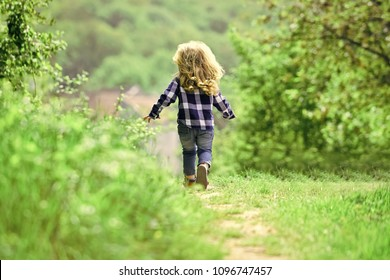 Childhood. Child run on path in spring or summer park. Boy with long blond hair on idyllic day. Childhood activity, leisure, lifestyle. Energy, growth, youth concept.