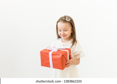 Childhood, children and holiday concept - little girl in white dress with gift box on white background