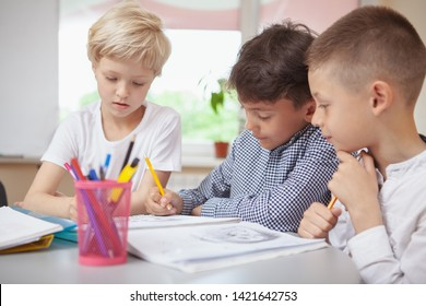 Childhood, communication concept. Group of little kids working on art project together. Two schoolboys and a girl sketching for art class homework